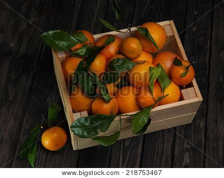 Mandarins in a wooden box on wooden background