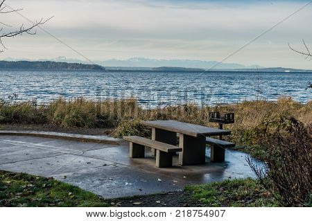 A picnic table sits on shore at Seahurst Park in Burien Washington. The Olympic Moountains can be seen across the Puget Sound.