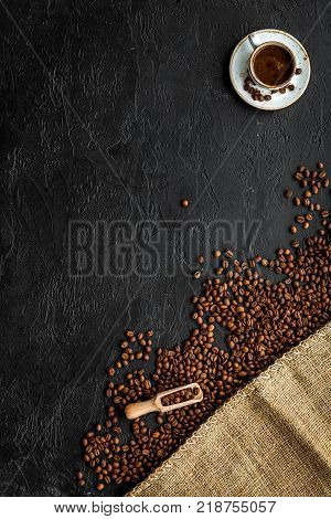 Coffee concept. Roasted beans, canvas, cup of espresso on black background top view.