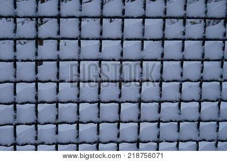 mesh netting. Rabitz covered with snow, background, texture. Rusty fence Rabitz.fence made of wire mesh, netting covered with white on background of blue sky.
