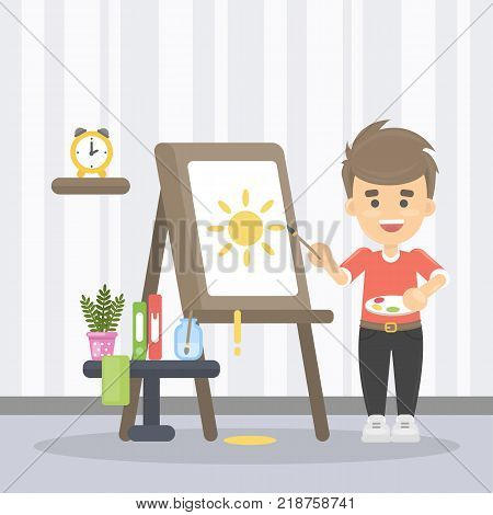 Boy drawing the sun at home on the board with brush.