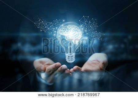 Light Bulb With Brain Inside The Hands Of The Businessman.
