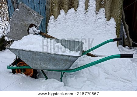 an iron wheelbarrow with snow and a big shovel in the winter yard