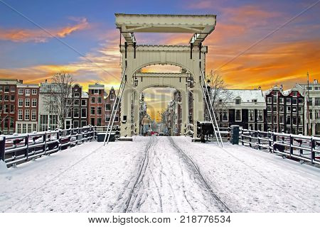 Snowy tiny bridge in Amsterdam the Netherlands in winter at sunset