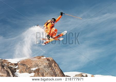 An athlete skier is jumping from high rock high in the mountains. Fluff powder from the snow behind the flying athlete