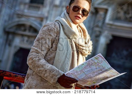 Rediscovering things everybody love in Milan. elegant tourist woman in fur coat and sunglasses in the front of Duomo in Milan Italy looking at the map