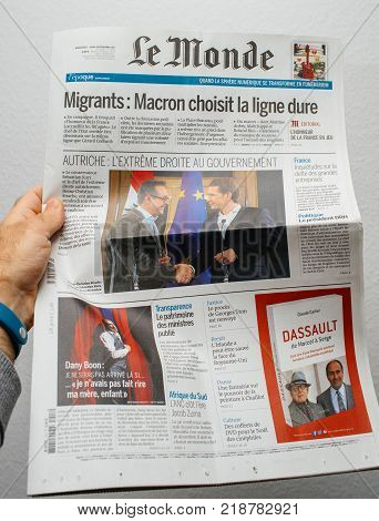 PARIS FRANCE - DEC 18 2017: Man reading Le Monde French cover newspaper with headlight and picture about new Chancellor of Austria Sebastian Kurz and Heinz-Christian Strache Austria's vice chancellor