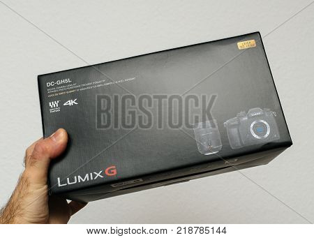 PARIS FRANCE - DEC 18 2017: Man holding Panasonic Lumix GH5 kit with Leica lens cardboard box received by post