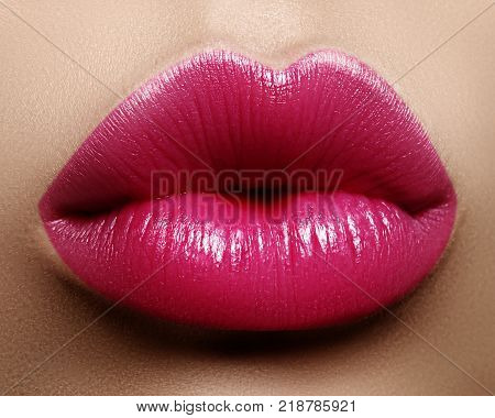 Close-up perfect lip makeup beautiful female mouth. Plump sexy full lips. Macro photo face detail. Perfect clean skin fresh lip make-up. Sweet pink lipstick magenta color. Valentine's day style