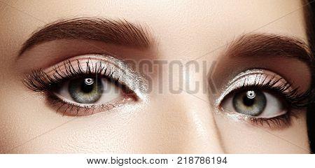 Closeup female eyes with bright make-up great shapes brows extreme long eyelashes. Celebrate makeup luxury eyeshadows. Macro of beautiful eye. Good vision