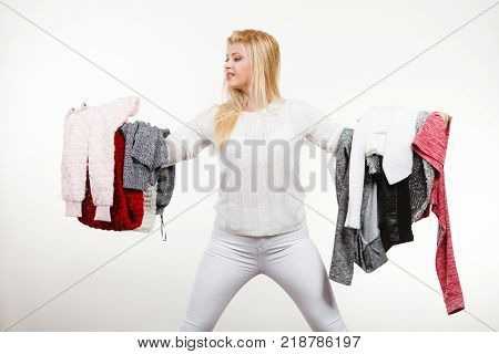 Fashion clothes dilemmas concept. Woman holding big pile of warm winter clothing cant decide what to wear on white grey