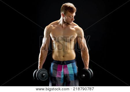 Concentrated man doing dumbbell workout. Well trained body with bulky muscles. Sport equipment and weightlifting.