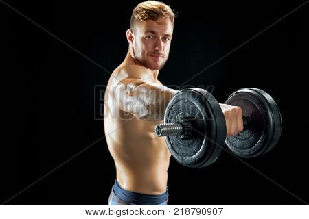 Alternating dumbbell front raise. Confident sportsman working on his body at the gym. Fitness and persistence.
