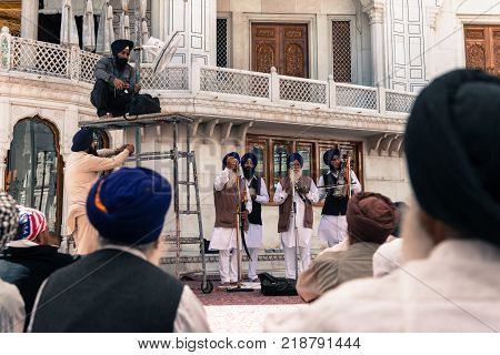 AMRITSAR INDIA - MARCH 21 2016: Sikh people playing music at Sri Harmandir Sahib known as Golden Temple located in Amritsar Punjab India.