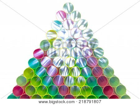 Many colorful straws stacked on top of each other of pyramid. Beyond the straw penetrates the white light across the straw.