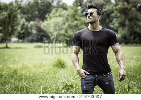 Handsome Muscular Hunk Man Outdoor in City Park or Countryside, Sitting on Grass. Showing Healthy Muscle Body While Looking away
