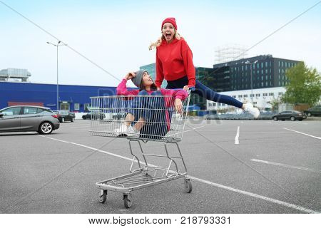 Two happy hipster girls having fun with shopping cart outdoors