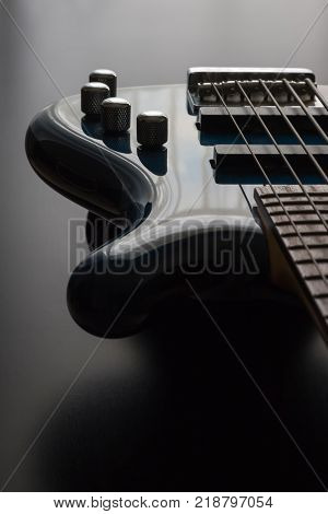 A Blue Bass Guitar Positioned Against A Dark Wooden Background