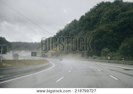 Asphalt slippery highway in rainy weather with cars on the road
