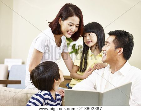 asian parents mother and father and two children son and daughter reading a book telling a story together.