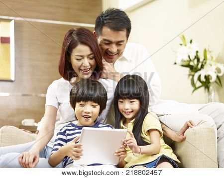 asian parents mother and father and two children son and daughter sitting on family couch using digital tablet together.