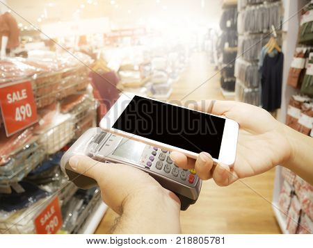 Mobile Payment Concept Shopping Online Concept : Hand holding smartphone paying on EDC machine at a fashion shop.