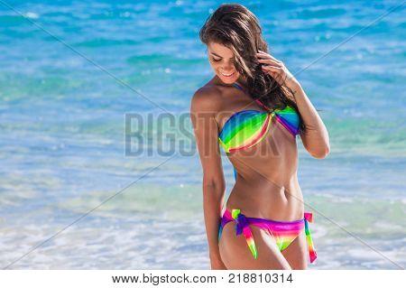 Beautiful happy girl in bikini walking in tropical sea waves