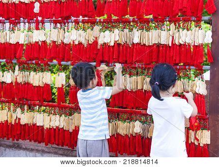 China Sanya - 15 Nov 2017: Chinese children hang EMA in a Buddhist temple