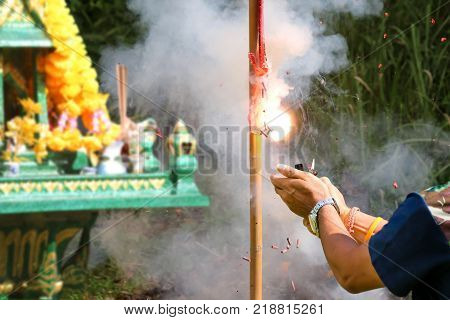 Asian people pay respect to shrine of the household god or spirit worship Incense and firecrackers