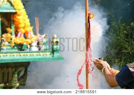 Asian people pay respect to shrine of the household god or spirit worship and firecrackers