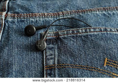Earphones in a back pocket of a jean