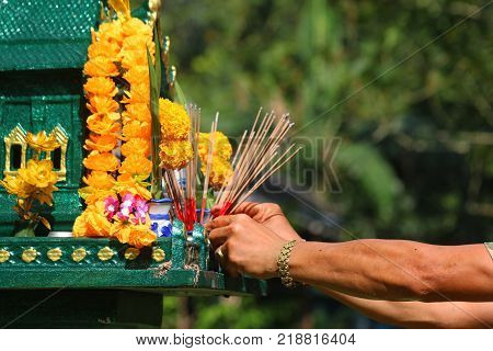 Asian people pay respect to shrine of the household god or spirit worship and firecrackers.