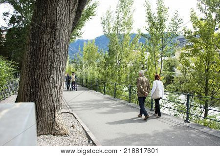 Italian People And Foreigner Travelers Walking Relax On Footpath At Riverside Of Passer River In Mer