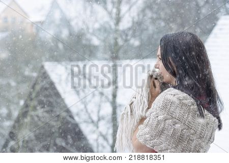 Woman squeezes her shawl enjoying the snow - Beautiful young brunette woman grasping her shawl around her body and face while enjoying a fairytale snowfall. poster