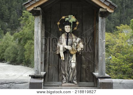 St. Lukas statue in wooden cottage on old bridge over Bad inn river at Pfunds village in evening time in Tyrol Austria