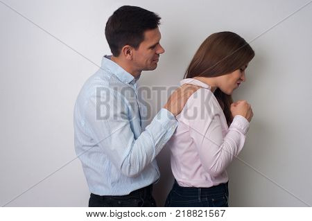 Husband and wife are quarreled. Handsome man asks forgiveness for angered wife in casual clothes on white background
