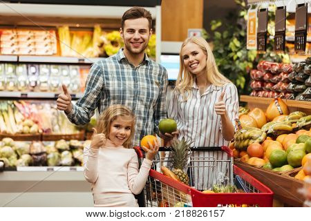Happy family choosing groceries and showing thumbs up gesture while standing in the supermarket