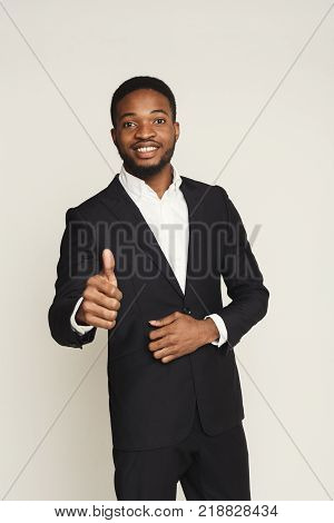 I like it. Happy smiling black man showing thumb up gesture, man portrait in formal wear, standing on white background, studio shot