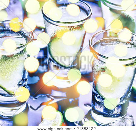 A party in the club. Cocktails on the bar. Alcohol. Vodka, gin, tequila with ice and lime. Alcoholic cocktail  cocktail. Selective focus glasses of cold vodka on black table with reflection