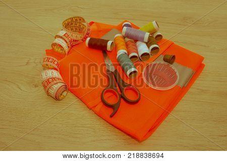 Sewing still life: colorful cloth. scissors and sewing kit includes threads of different colors thimble and other sewing accessories on wooden table. tools for sewing for hobby - Retro color