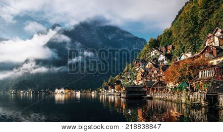 Scenic view of famous Hallstatt lakeside town reflecting in Hallstattersee lake in the Austrian Alps in morning light in autumn with clouds Salzkammergut region Austria