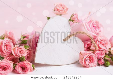 Tender pink roses flowers and decorative white heart. Selective focus. Place for text.