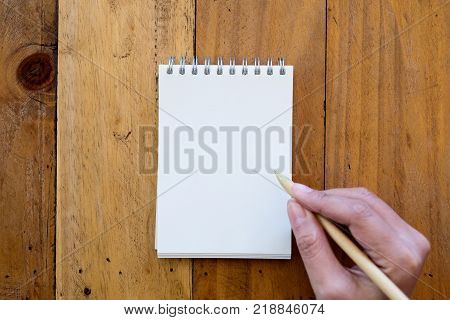 Top view image of a hand holding a pen and going to write on a blank white notebook on wooden background
