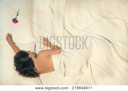 Beautiful naked female sleeping in bed. Flower on a pillow near a beautiful girl. View from above. A conceptual photography of the relationship between a man and a woman.