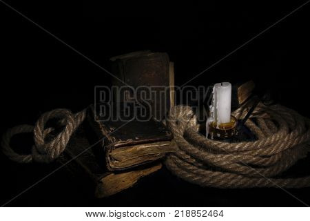 extinguished wax candle with a wick old shabby book twisted rope on a black background