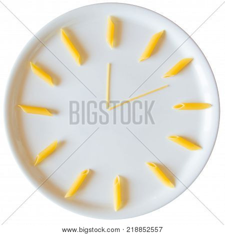 Uncooked italian pasta penne in clock shape on dish on white background