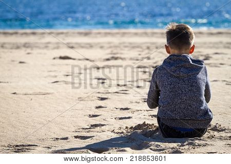 Sad alone boy sitting on the beach, looking at sea and thinking