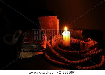 burning wax candle with a wick old shabby book twisted rope on a black background