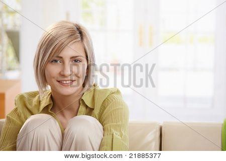 Porträt der lächelnde Frau sitzend mit Arme um die Knie im Wohnzimmer, Blick in die Kamera.?