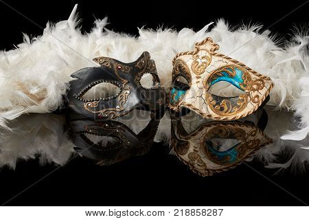 venetian carnival mask with white feathers on black background